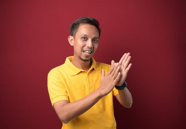 Молодой азиатский мужчина в повседневной одежде аплодирует счастливыми и радостными улыбающимися гордыми руками вместе