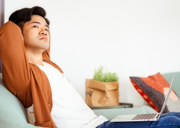 Young asian man wearing casual clothes and using laptop