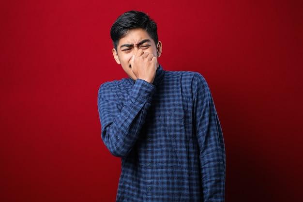 赤い背景の上にカジュアルなシャツを着た若いアジア人男性は、臭い、嫌な、耐え難い匂いを嗅ぎ、鼻に指で息を止めます。悪臭
