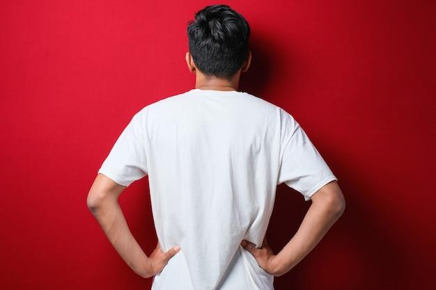 赤い背景の上にカジュアルなシャツを着て後ろ向きに立っている若いアジア人男性