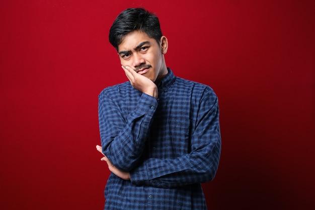 赤い背景の上にカジュアルなシャツを着ている若いアジア人男性は、腕を組んでうつ病の問題に疲れて退屈しているように見えると考えています。