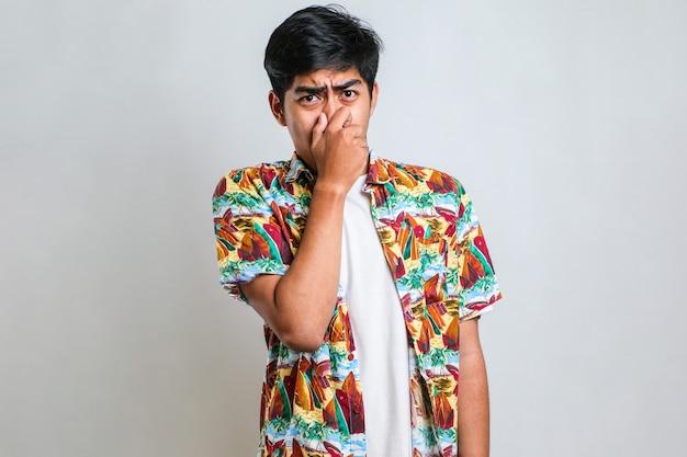 白い背景の上にカジュアルなシャツを着た若いアジア人男性は、臭い、嫌な、耐え難い匂いを嗅ぎ、鼻に指で息を止めます。悪臭