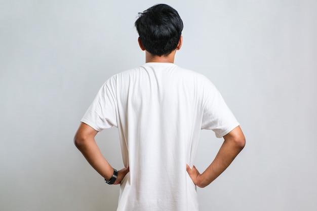 白い背景の上にカジュアルなシャツを着て後ろ向きに立って体に腕を持って目をそらしている若いアジア人男性
