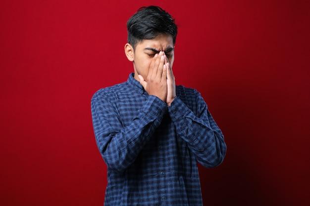倦怠感と頭痛、眠くて疲れた表情のために目をこすりながら孤立した赤い背景の上に立っているカジュアルなシャツを着ている若いアジア人男性。視力の問題