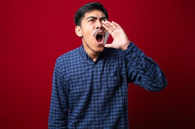 Молодой азиатский мужчина в повседневной рубашке кричит и громко кричит в сторону с рукой за рот на красном фоне. концепция коммуникации.
