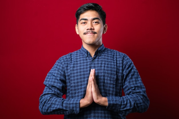 赤い背景の上の挨拶と歓迎のジェスチャーでカジュアルなシャツを着ている若いアジア人男性