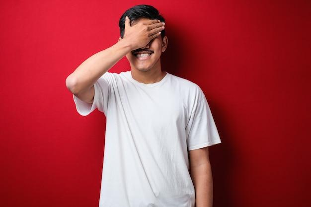 片目を手で覆うカジュアルな白いtシャツを着て、赤い背景の上に、自信を持って笑顔と驚きの感情を身に着けている若いアジア人男性。
