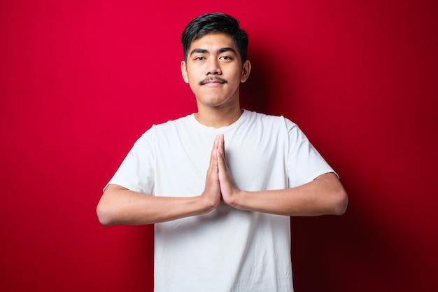 挨拶と赤い背景の上の歓迎のジェスチャーでカジュアルな白いtシャツを着ている若いアジア人男性