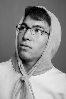 カラフルなパーカーと眼鏡を身に着けている若いアジア人