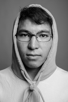 Young asian man wearing colorful hoodie and eyeglasses
