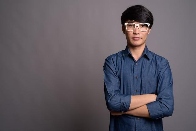 灰色の壁に対してスマートに見える眼鏡をかけている若いアジア人男性
