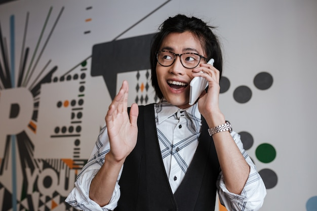 Young asian man wearing glasses talking by mobile phone
