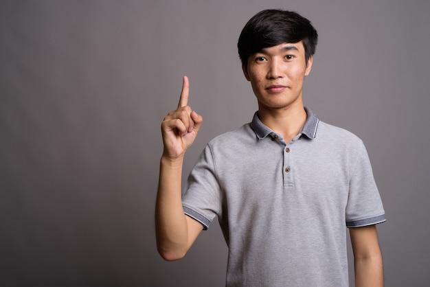 灰色の壁に灰色のポロシャツを着ている若いアジア人男性