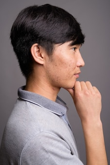 Young asian man wearing gray polo shirt against gray wall
