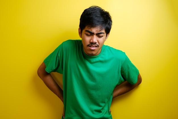 Молодой азиатский мужчина в зеленой футболке с болями в пояснице, потирая спину, измученный концепцией. желтый фон