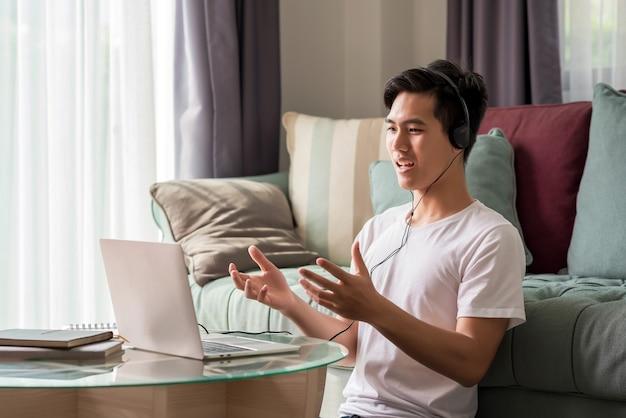 ヘッドフォンを身に着けている若いアジア人男性は、自宅のラップトップを介してオンライン研究に取り組んでいます。