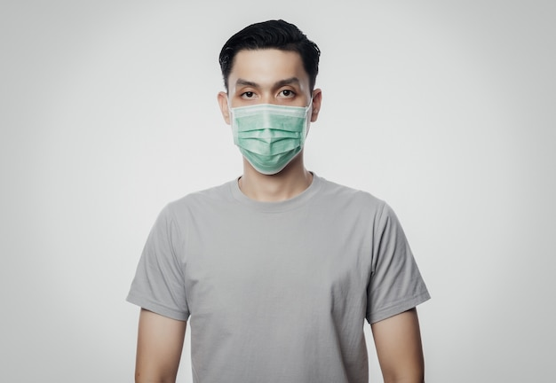 Молодой азиатский мужчина в гигиенической маске для предотвращения инфекции, 2019-нков или коронавируса. заболевание дыхательных путей, такое как борьба с гриппом 2.5 и грипп. студия выстрел изолированные на белой стене