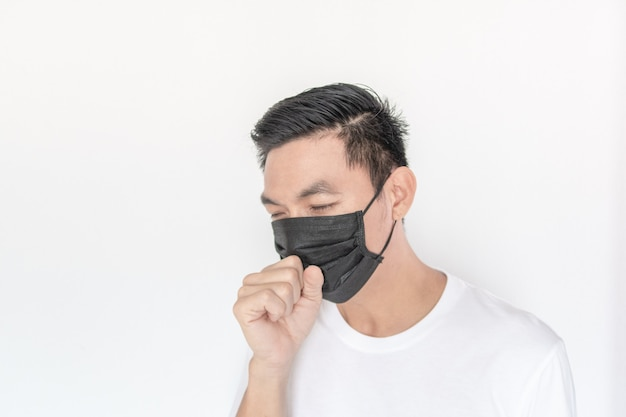 Young asian man wearing mask and coughing