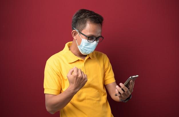 스마트폰으로 의료용 마스크를 쓴 젊은 아시아 남성이 자랑스럽게 비명을 지르며 승리를 축하합니다.