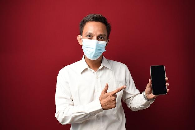 스마트폰을 사용하여 의료용 마스크를 쓴 젊은 아시아 남성은 손과 손가락으로 가리키며 매우 행복합니다.