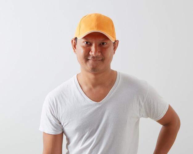 A young asian man wearing an orange cap on light grey wall
