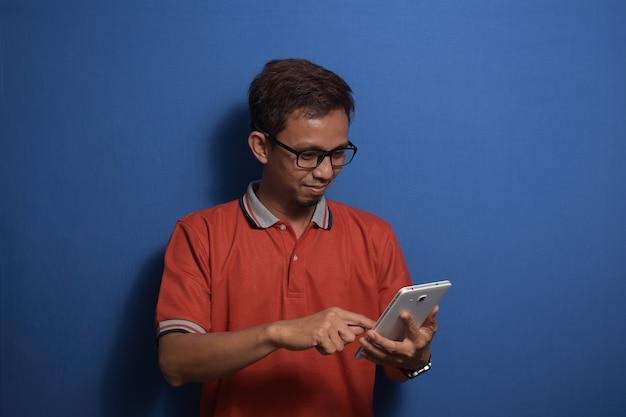 좋은 소식에 웃는 얼굴로 스마트 폰을 사용하여 주황색 캐주얼 티셔츠를 입은 젊은 아시아 남자