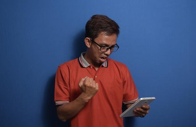 주황색 캐주얼 티셔츠를 입은 젊은 아시아 남성은 태블릿을 사용하여 자랑스럽게 비명을 지르고 승리를 축하합니다