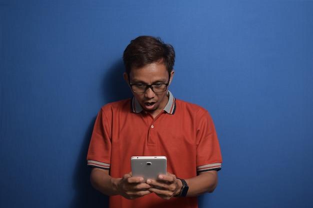 태블릿을 사용하여 주황색 캐주얼 티셔츠를 입은 젊은 아시아 남성은 그가 받은 좋은 소식에 충격을 받았습니다.