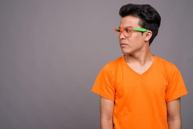 Молодой азиатский мужчина в оранжевой рубашке