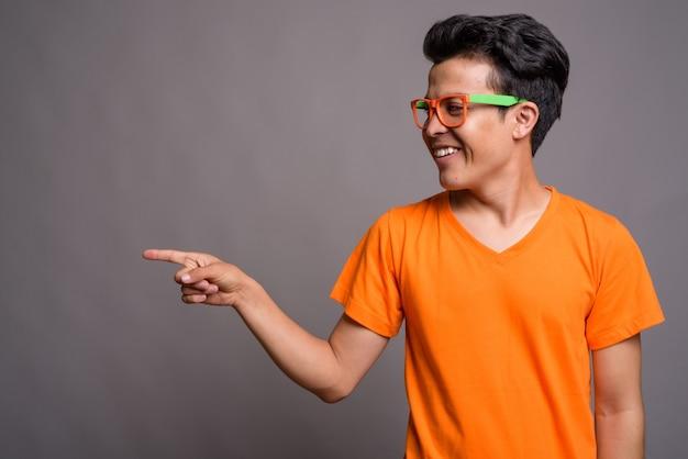 Young asian man wearing orange shirt