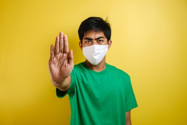 공유 사기, 가짜 뉴스를 막기 위해 중지 제스처를 하는 보호 마스크를 쓴 젊은 아시아 남자