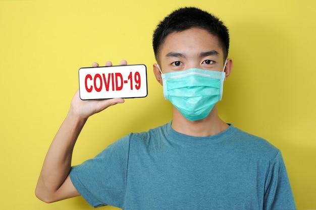 黄色の背景で隔離、彼の頭の横にある電話画面にcovid-19テキストを示す保護マスクを身に着けている若いアジア人