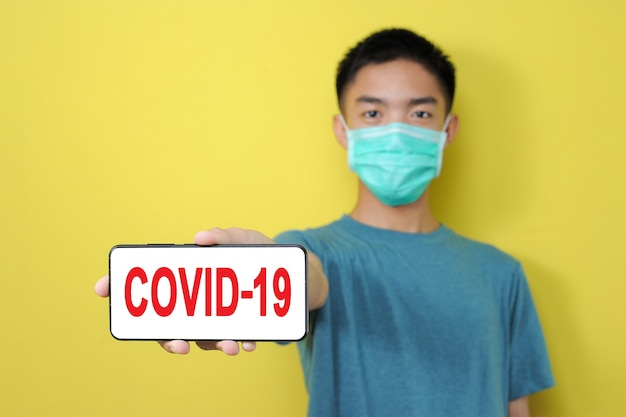 黄色の背景で隔離の電話画面にcovid-19テキストを表示する保護マスクを身に着けている若いアジア人男性