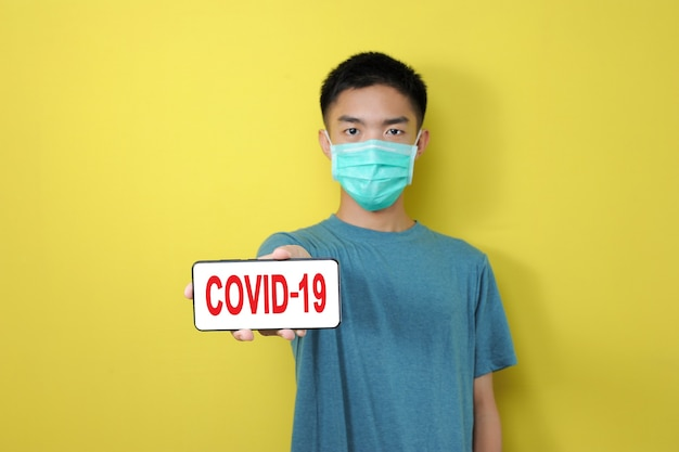 Young asian man wearing protect mask showing covid-19 text on phone screen, isolated on yellow background