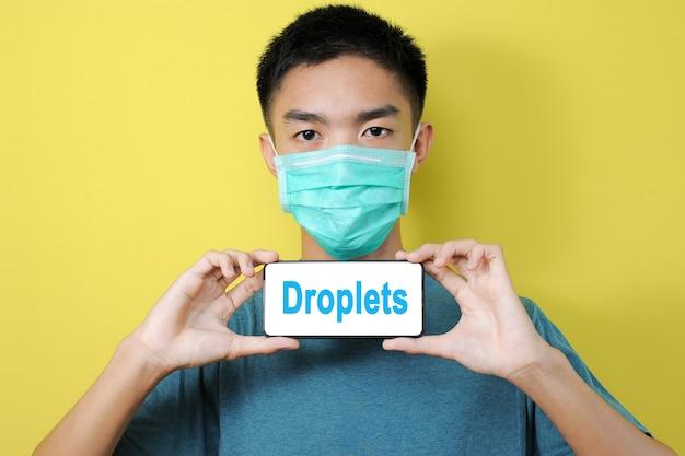 黄色の背景で隔離の電話画面に飛沫のテキストを表示する保護マスクを身に着けている若いアジア人