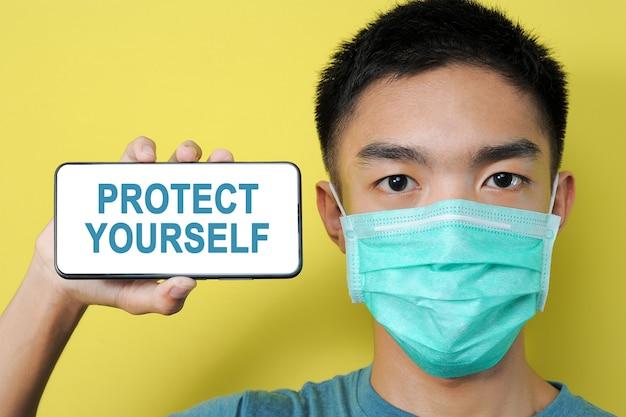 保護マスクを身に着けている若いアジア人男性は、黄色の背景で隔離、彼の頭の横にある電話画面に自分自身を保護するテキストを表示