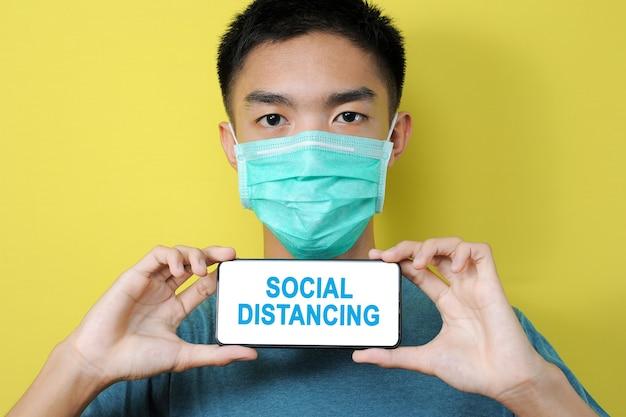黄色の背景で隔離の電話画面に社会的距離のテキストを表示する保護マスクを身に着けている若いアジア人男性