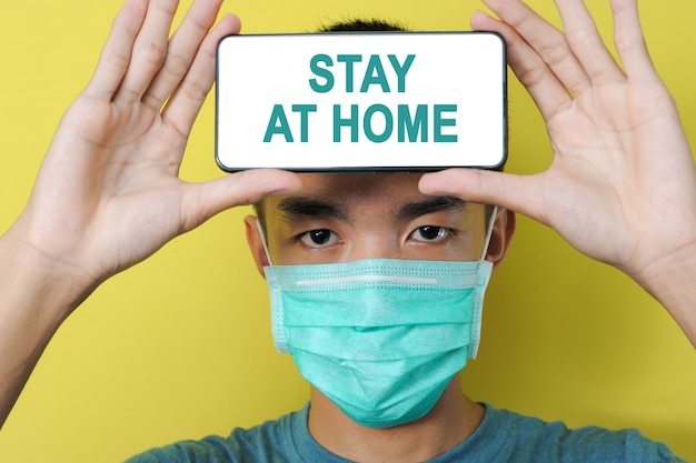 黄色の背景で隔離の彼の額の前の電話画面に外出禁止令のテキストを表示する保護マスクを身に着けている若いアジア人