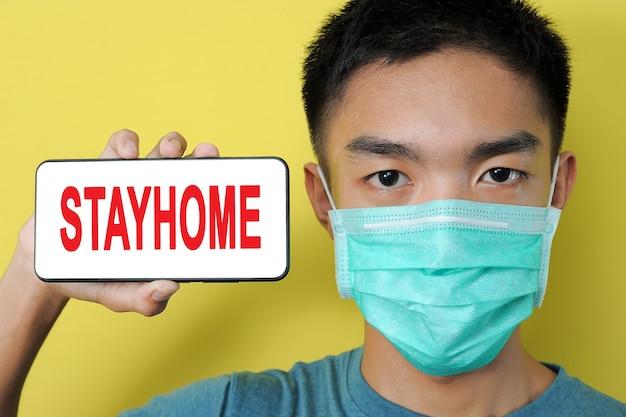 黄色の背景で隔離、彼の頭の横にある電話画面にstayhomeテキストを表示する保護マスクを身に着けている若いアジア人