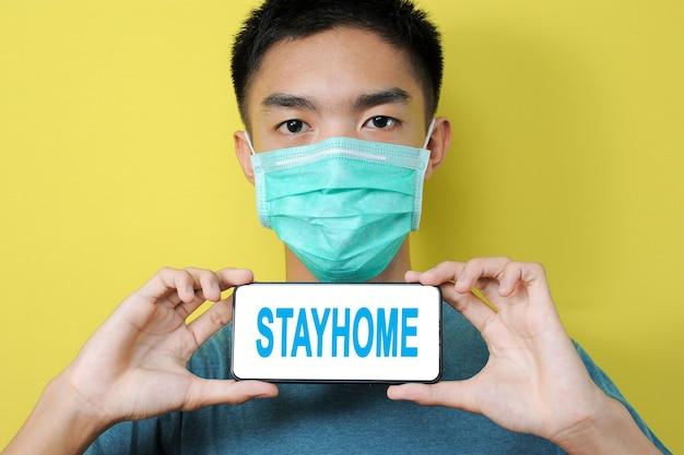 黄色の背景で隔離の電話画面にstayhomeテキストを表示する保護マスクを身に着けている若いアジア人男性