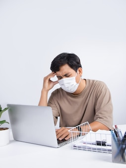 Young asian man wearing a protective mask, feels bad in the office, he has a stressful headache from working. studio shot isolated on white background.