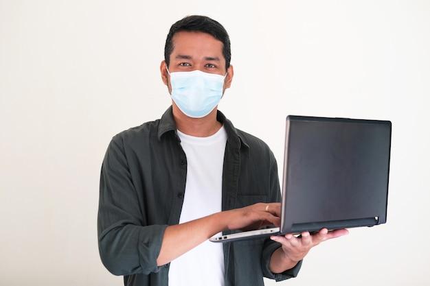 ラップトップコンピューターを保持しながら保護医療マスクを身に着けている若いアジア人男性