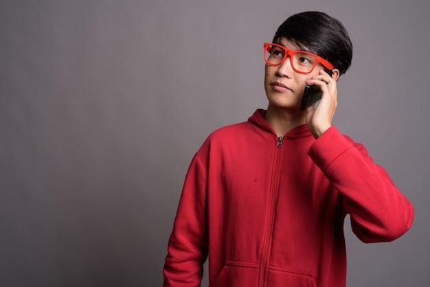 Молодой азиатский мужчина в красной куртке с очками на сером