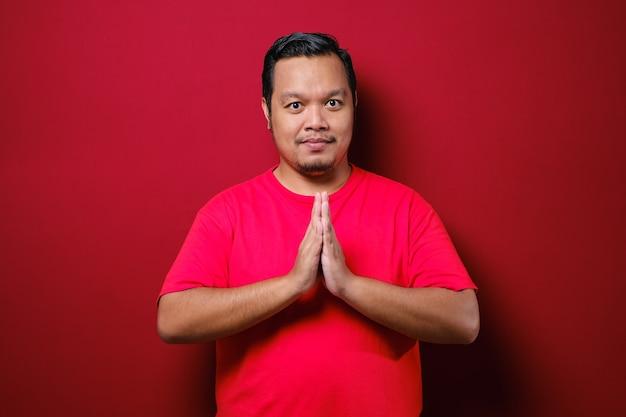 赤い背景で隔離の挨拶と歓迎のジェスチャーで赤いtシャツを着て若いアジア人男性
