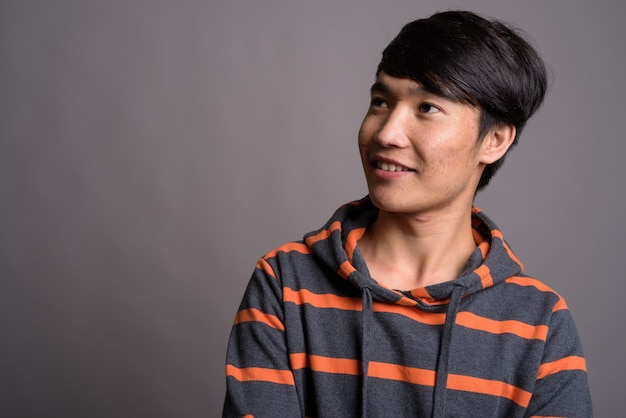 회색 벽에 줄무늬 까마귀를 입고 젊은 아시아 남자