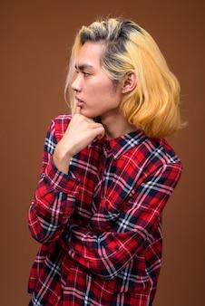 Молодой азиатский человек нося стильную одежду против коричневой предпосылки