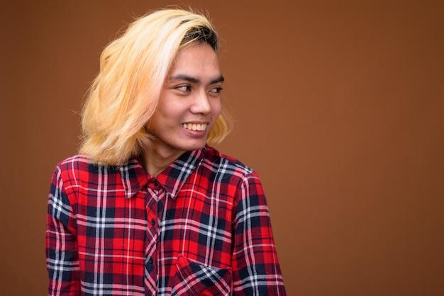 茶色の背景にスタイリッシュな服を着ている若いアジア人