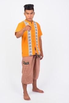 Молодой азиатский мужчина в традиционной одежде у белой стены