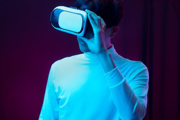 Молодой азиатский человек в очках виртуальной реальности смотрит видео 360 градусов в неоновом свете, концепция технологии.
