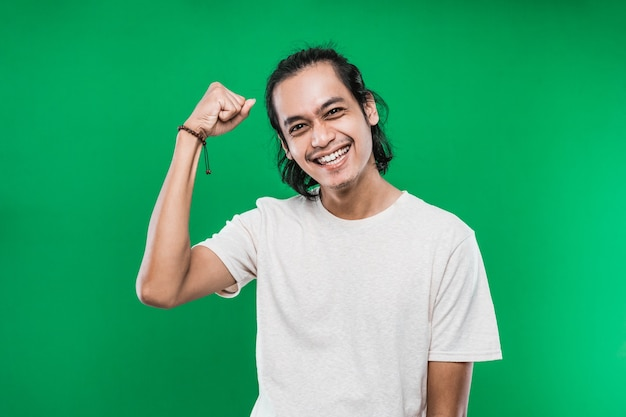 Young asian man wearing white casual t-shirt posing clenching fists doing winner gesture isolated on green background
